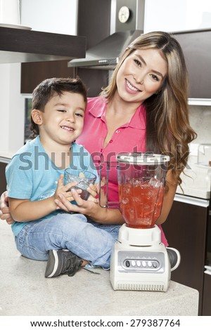 Mother and son in the kitchen of his home with blender - stock photo
