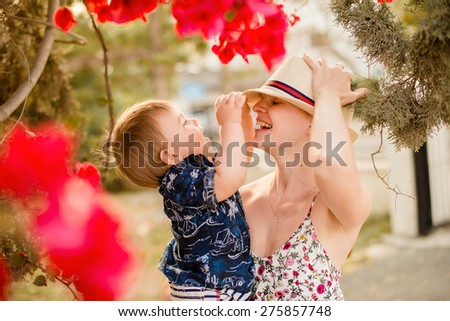 Mother and son laughing together in a beautiful flowered garden - stock photo