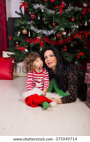 Mother and son laying in front of Christmas tree,son looking at mother