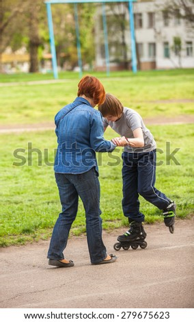 mother and son learn to roller skate. Mom with child having fun on roller skates