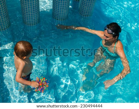 Mother and son learning to swim in the pool - stock photo