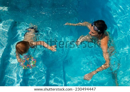 Mother and son learning to swim in the pool. the child dives