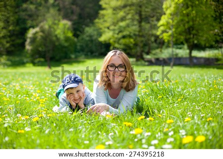 Mother and son lie on the grass - stock photo