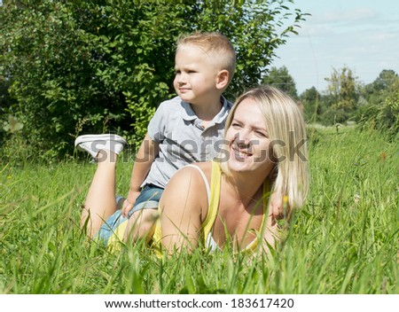 mother and son lie on the grass green grass and looking in the same direction