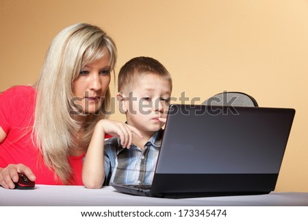 Mother and son looking at a laptop against an orange background.