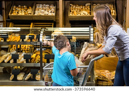 Mother and son looking at bread in grocery store - stock photo