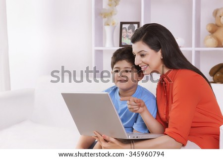 Mother and son looking at laptop - stock photo
