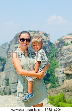 Mother and son looking at the town of Kalambaka bird's eye view. Vertical view. Meteora, Greece. - stock photo