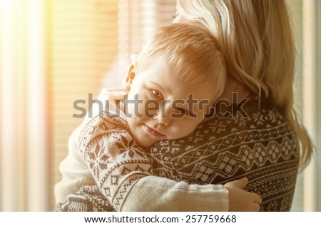 Mother and son lookings near the window. - stock photo