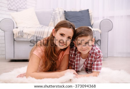 Mother and son lying on the carpet beside sofa in the room - stock photo