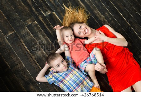 Mother and son lying on the floor holding each other and smilingMom and sons lying on the floor in colored clothing - stock photo