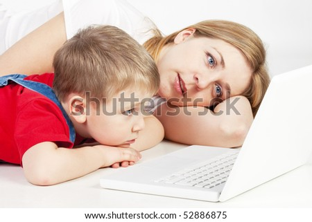 Mother and son lying on the floor with laptop on white background