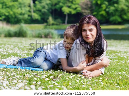 Mother and son lying on the grass in a park in bright sunny day