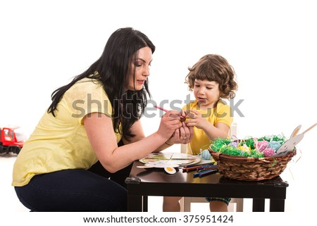 Mother and son making Easter decorations  in their home - stock photo
