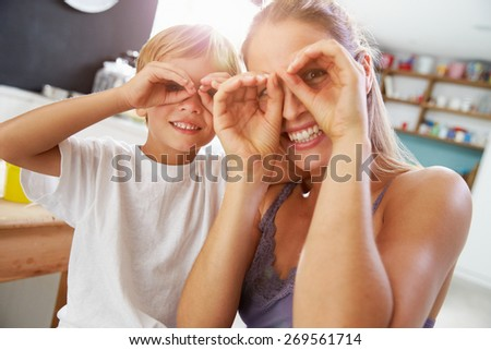 Mother And Son Making Funny Faces At Breakfast Table - stock photo