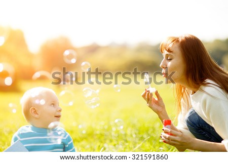 Mother and son making soap bubbles outdoors in park - stock photo