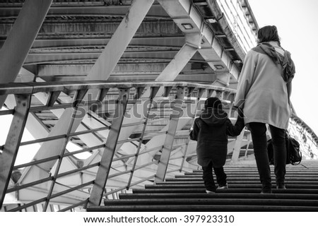 Mother and son on pedestrian Solferino bridge over Seine River near Orsey's Museum. Paris, France. Back view. - stock photo