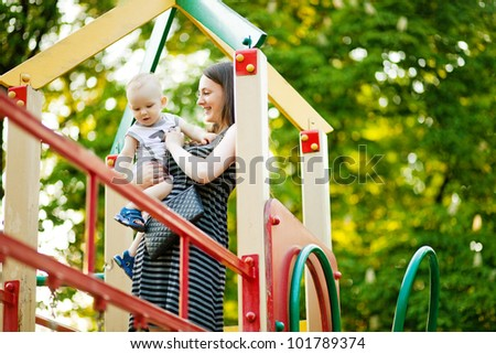 Mother and son on playground - stock photo