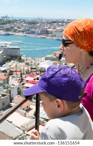 Mother and son on the urban landscape with a lot of houses and the river - stock photo