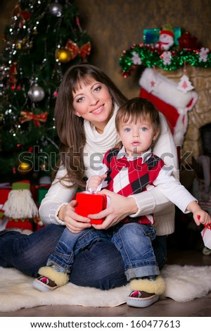 mother and son opening Christmas presents. smiling and looking into the camera