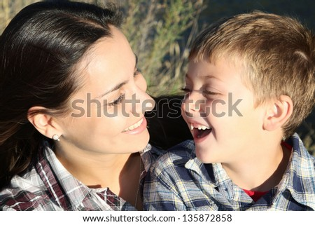 Mother and son outside in the sun having fun - stock photo