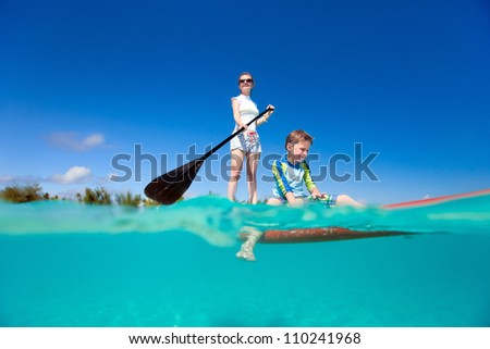 Mother and son paddling on stand up paddle board - stock photo