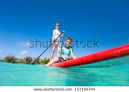 Mother and son paddling on stand up paddle board at tropical ocean - stock photo