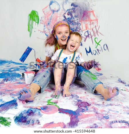 Mother and son paint the walls. Child himself dirty in the paint and looks into the camera. Child has fun and stain the wall. Children's creativity. Art for baby. - stock photo