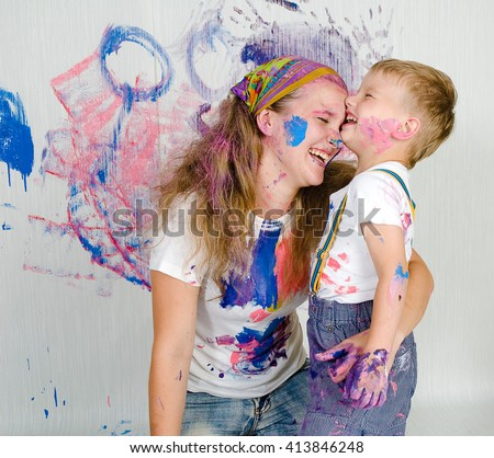 Mother and son paint the walls/ drawing on wall. Child himself dirty in the paint and looks into the camera. Child has fun and stain the wall. Children's creativity. Art for baby.