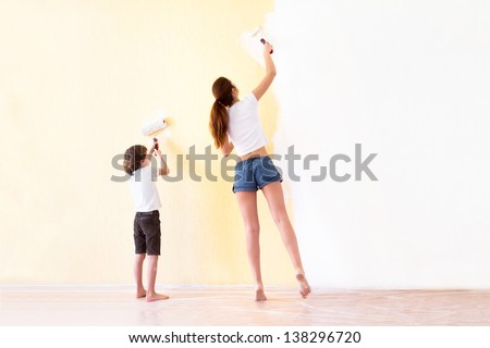 Mother and son painting walls in a new house - stock photo