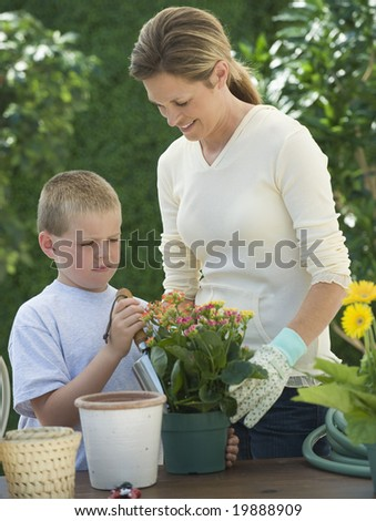Mother and son planting flowers - stock photo