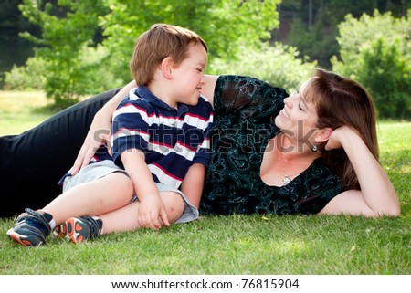 Mother and son play outside on field on Mother's Day. - stock photo
