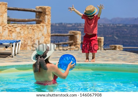 mother and son playing at the pool - stock photo