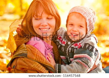 Mother and son playing in autumn park - stock photo