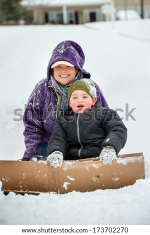 Mother and son playing in snow using cardboard box to slide down hill - stock photo