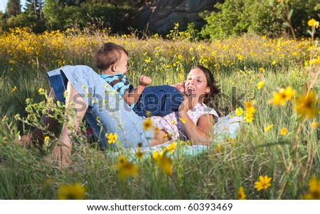 Mother and son playing, mother pretending that her son's feet are a telephone and she is speaking and listening. - stock photo