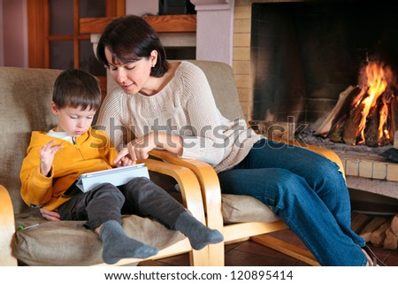 Mother and son playing on digital tablet PC  in front of fireplace - stock photo
