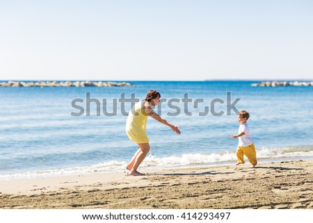 mother and son playing on summer tropical beach
