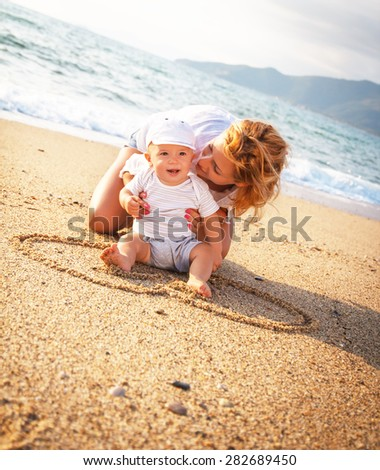 Mother and son playing on the beach - stock photo