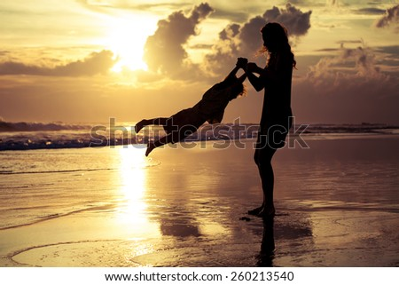 mother and  son playing on the beach at sunset time - stock photo