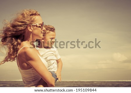 mother and  son playing on the beach at the day time - stock photo