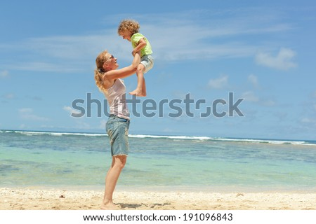 mother and  son playing on the beach in day time
