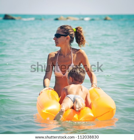 Mother and son playing on the beach with air mattress. - stock photo