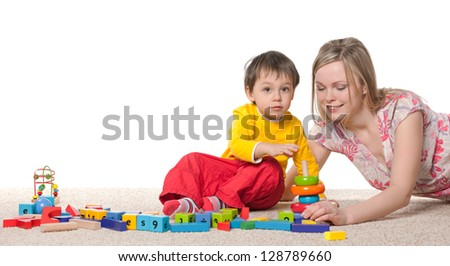 Mother and son playing on the carpet with toys - stock photo