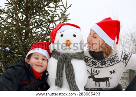 Mother and son playing snowman. Winter fun.