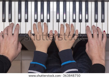 Mother and son playing the piano. Aerial view.