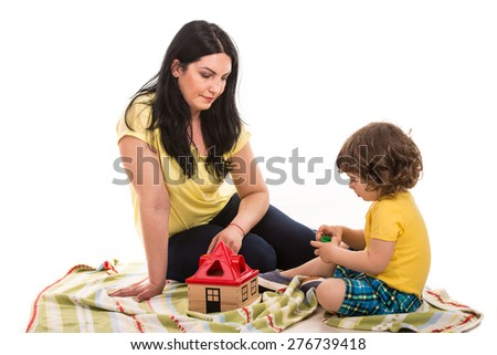 Mother and son playing together home and sitting on blanket - stock photo
