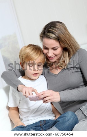 Mother and son playing video game on telephone
