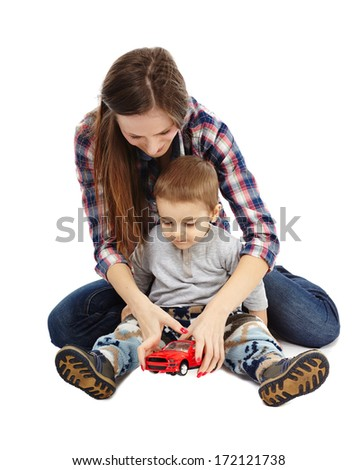 Mother and son playing with a toy car, sitting on floor - stock photo