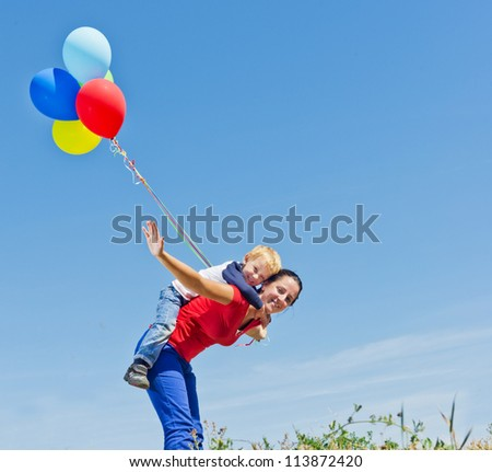 Mother and son playing with balloons in nature - stock photo